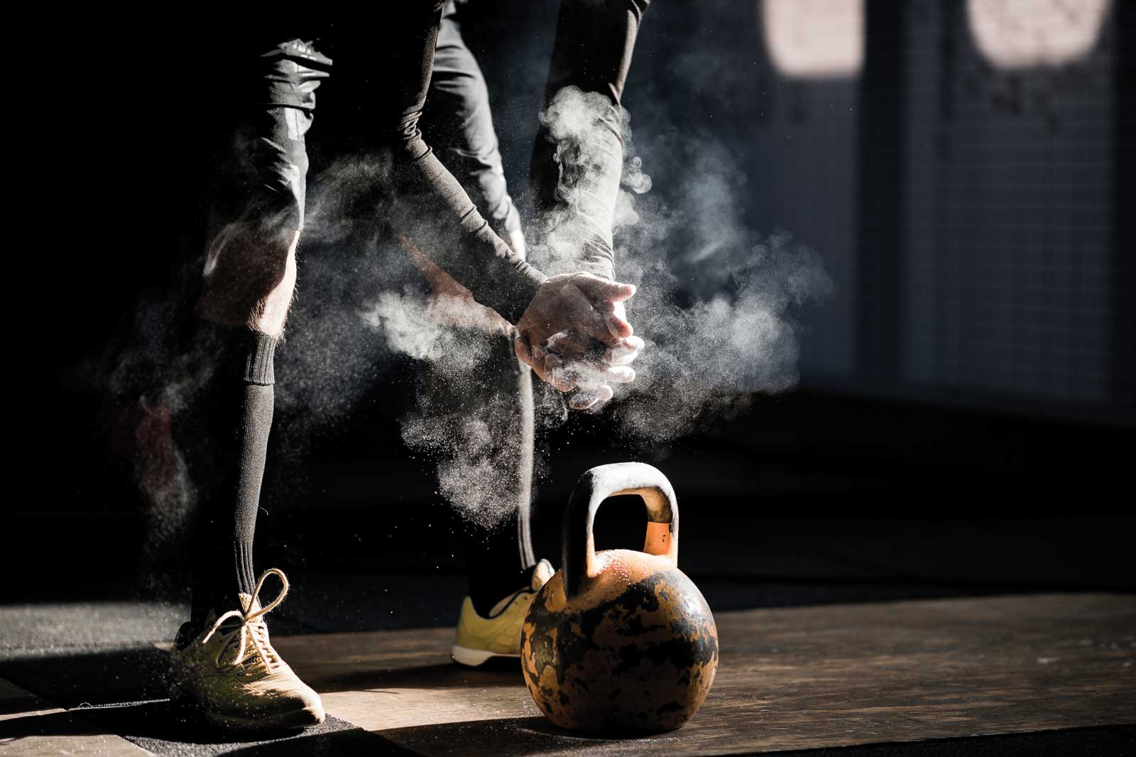 Man dusting hands over kettle bell